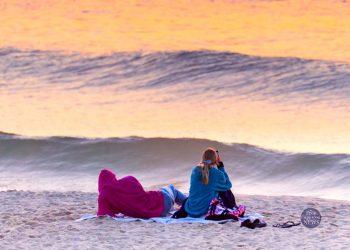 Cape Cod Weather tonight - July 31, 2020. Free Cape Cod News - Photo: Couple watching sunset on Cape Cod beach.